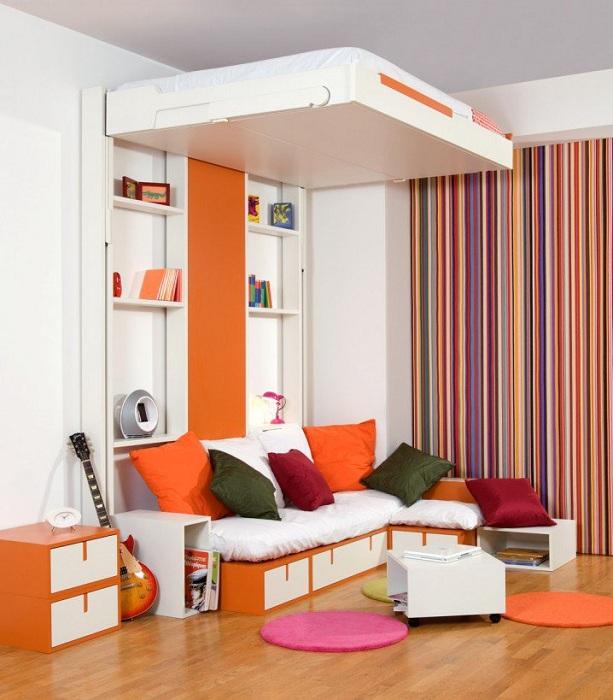 Симпатичный и яркий интерьер спальни с очень нестандартной кроватью оформленной в пестрых тонах.