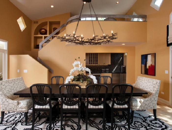 Интересное дизайнерское решение оформление столовой в черно-белых тонах с красивой люстрой из оленьих рогов.