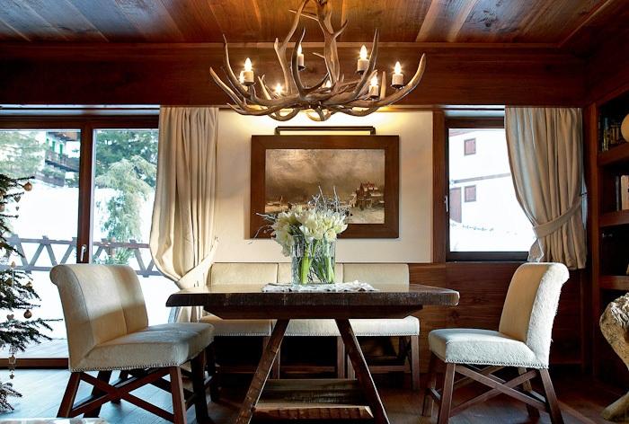 Светлая отделка мебели в гостиной с интересной люстрой с оленьих рогов.