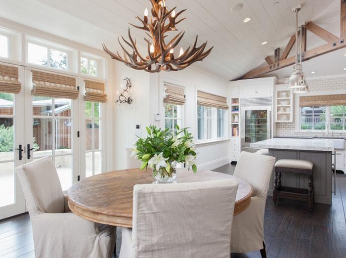 Светлая столовая с люстрой из оленьих рогов - креативная и уютная.