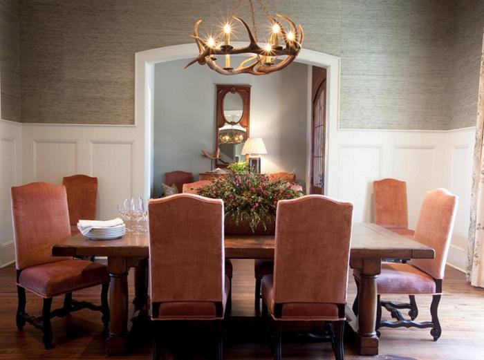Интересный интерьер столовой с персиковыми креслами и интересной люстрой.