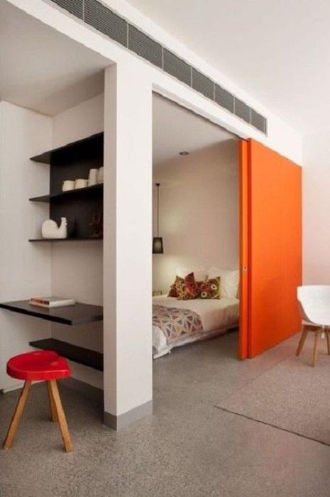Интересный интерьер гостиной и спальной создан благодаря просто невероятной яркой раздвижной двери.
