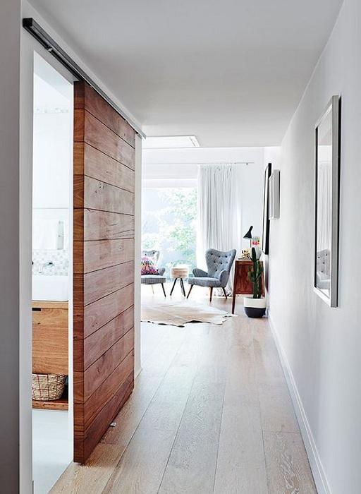 Крутое решение создать оригинальный интерьер в светлых тонах с применением деревянной двери.