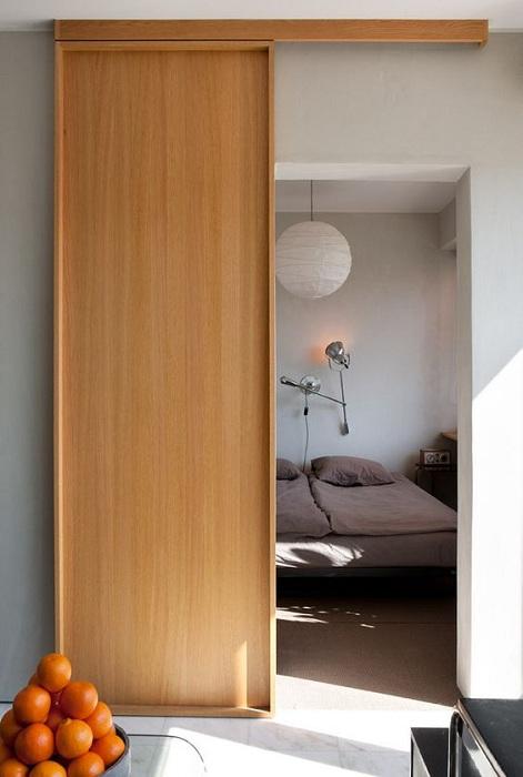 Красивое решение для того чтобы преобразить интерьер спальной при помощи оригинальной раздвижной двери.