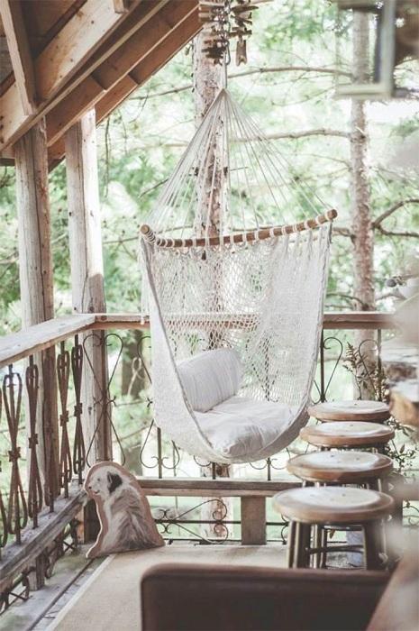 Прекрасный вариант оформления балкона с необычным креслом и рядом стульчиков.