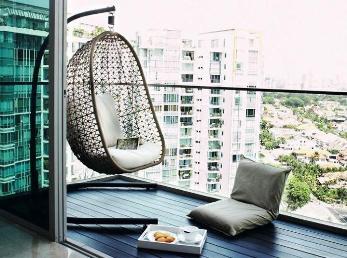 Балкон оформлен при помощи интересного кресла для отдыха, который отменно смотрится на нем.