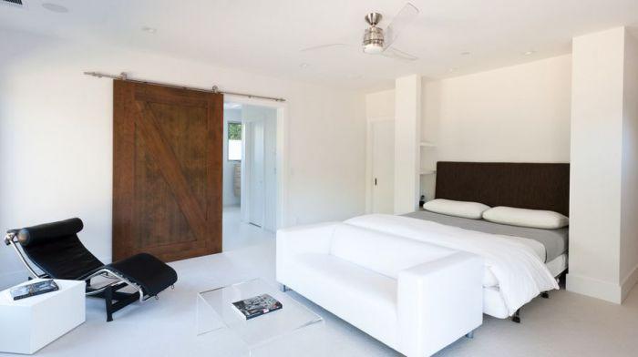 Светлый интерьер спальни дополняет интересная деревянная дверь, что позволяет создать более уютную обстановку.
