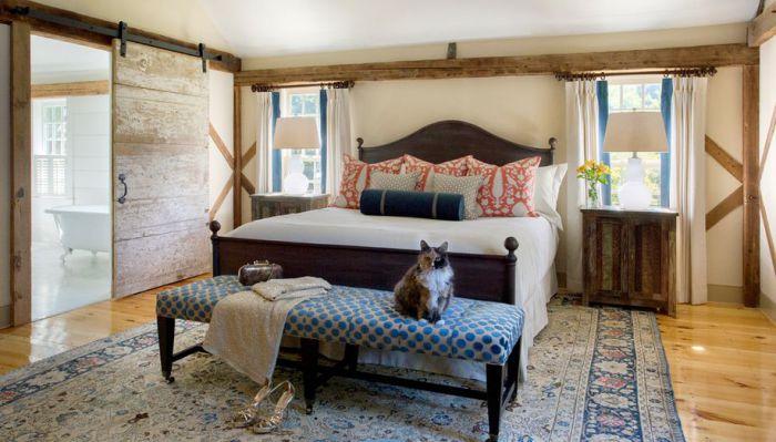 Прекрасный вариант оформления спальни в деревенском стиле с раздвижными оригинальными дверьми.