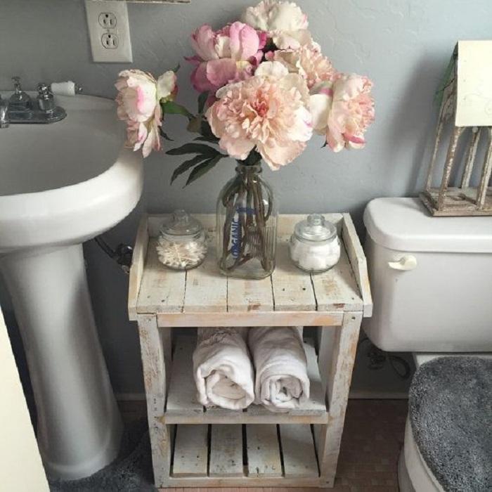Старый стол в ванной комнате, украшенный стеклянной бутылкой с искусственными цветами.