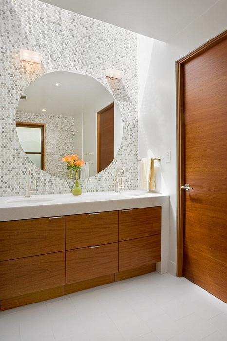 Использование светлых и темно-серых кусочков круглой мозаики визуально выделили большое круглое зеркало на стене ванной.