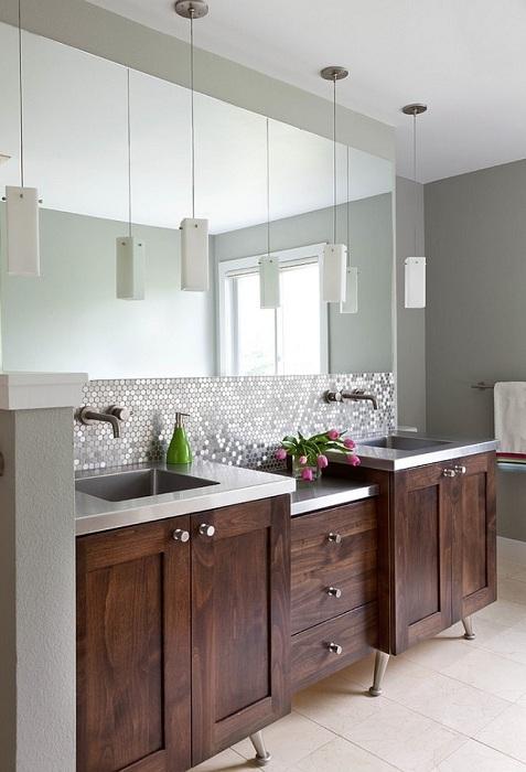 Оформление стен ванной комнаты блестящей серой круглой мозаикой, которая отлично сочетается с прямоугольной светлой плиткой, которой выложен пол ванной комнаты.