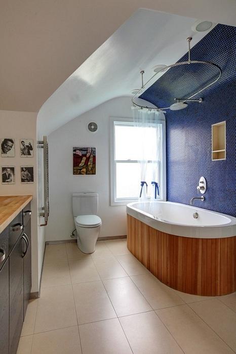 С помощью мозаики дизайнеры визуально выделили и акцентировали внимание на необычной овальной ванной, выложенной натуральным деревом.