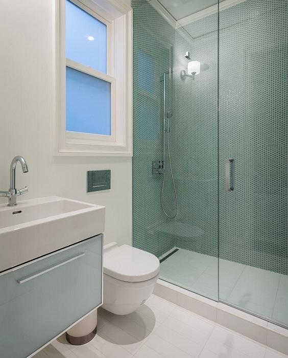 Стены душевой кабинки выложены темно-зеленой круглой мозаикой, которая отлично сочетается с белоснежной мебелью, полом, стенами и потолком ванной комнаты.