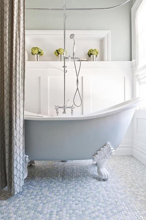 Стильная и элегантная ванная комната пол которой украшен круглой голубой плиткой светлых и темных тонов.