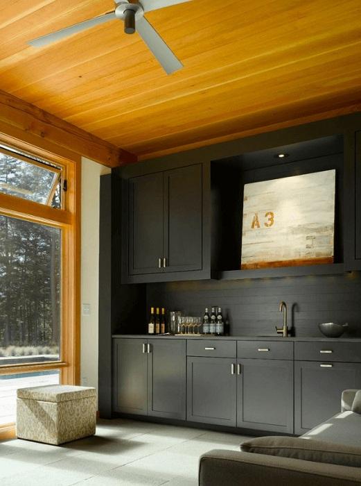 Большая и светлая кухня выполнена в черном цвете с применением дерева, что очень выиграшно смотрится.