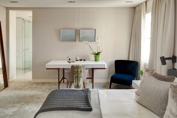 Светло-серый интерьер спальной подчеркивает особенный элемент декора - синее кресло.