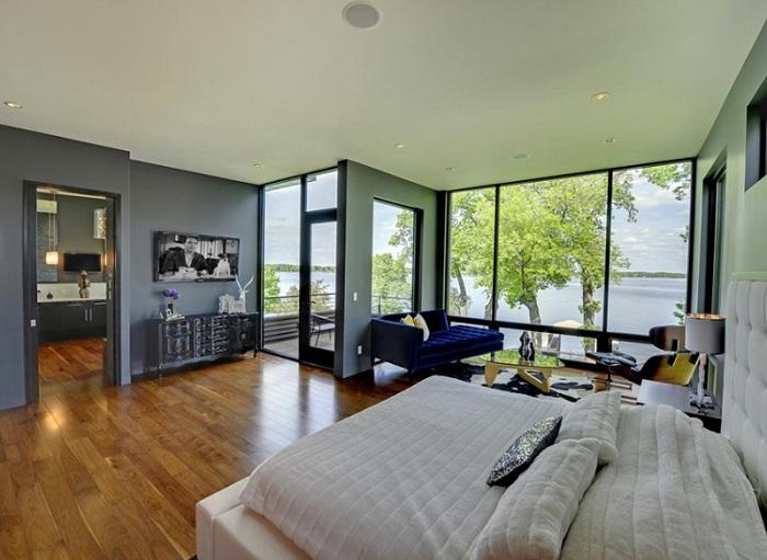 Прекрасный вид за окном спальной и интересный интерьер внутри с синим креслом.
