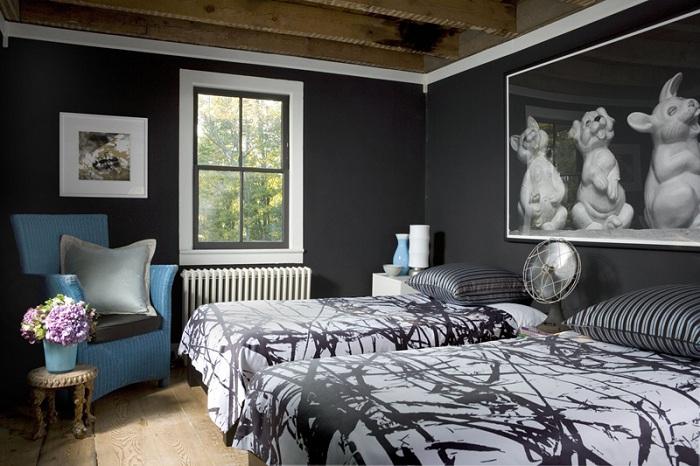 Прекрасная спальня в темных тонах с интересным креслом, которое украшает интерьер.