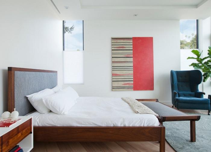 Простий і сучасний інтер'єр спальної доповнює синє крісло, яке затишно стоїть в кутку кімнати.