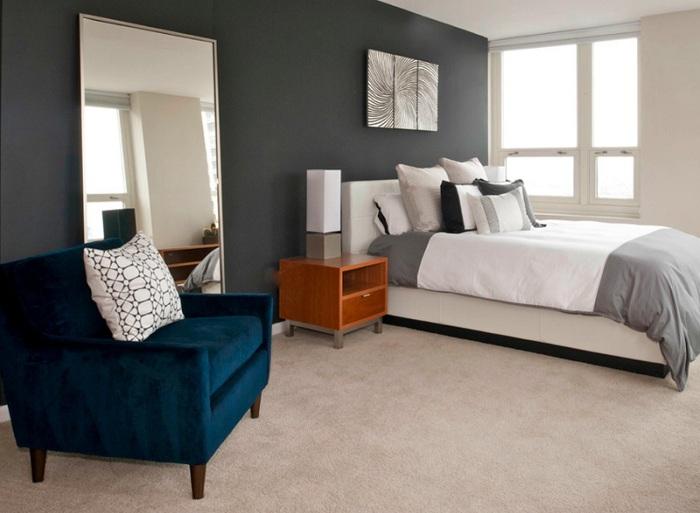 Отличный вариант оформления стенки в темно-сером цвете и интересный элемент декора комнаты - синее кресло.