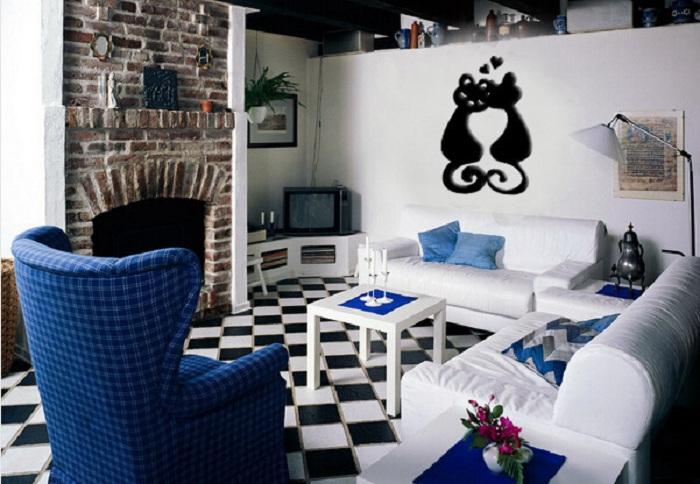 Красивый черно-белый интерьер с каменной кладкой на стене и интересным синим креслом.