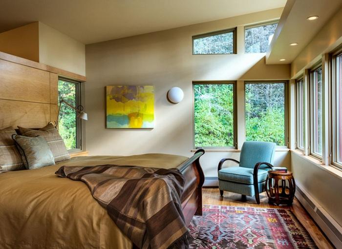 Интересный вариант оформления спальной в коричневых тонах с интересным креслом в синем цвете, который стал изюминкой.