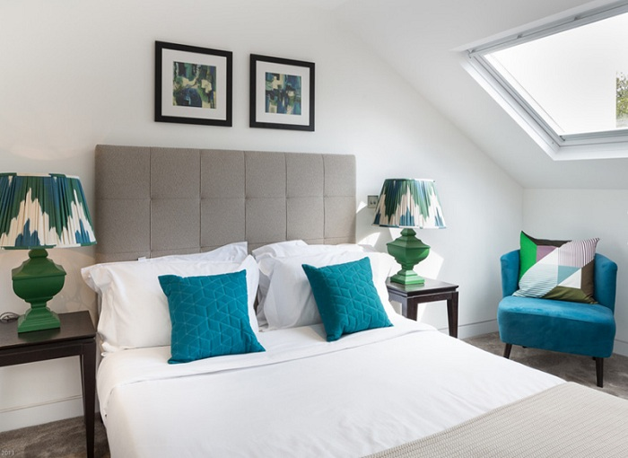 Светлая атмосфера спальной дополнена интересными яркими подушками и прекрасным креслом в синем цвете.