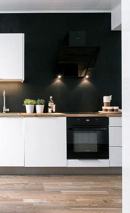 Оригинальный интерьер современной кухни с нестандартной черной стеной.