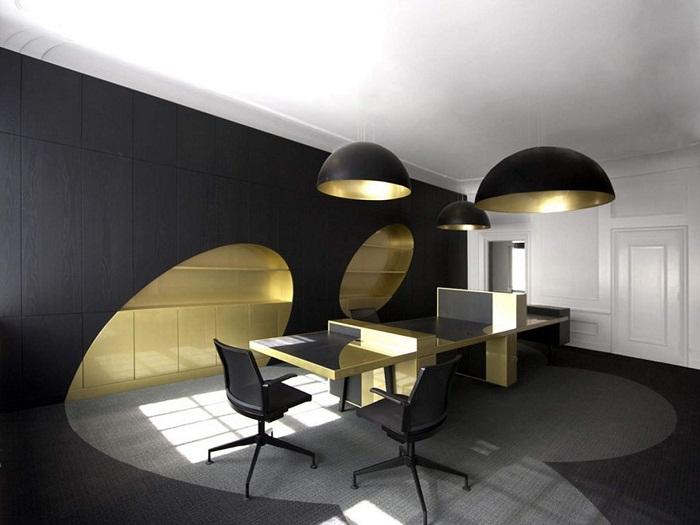 Нестандартное оформление офисного помещения с черной стеной и золотыми фрагментами.