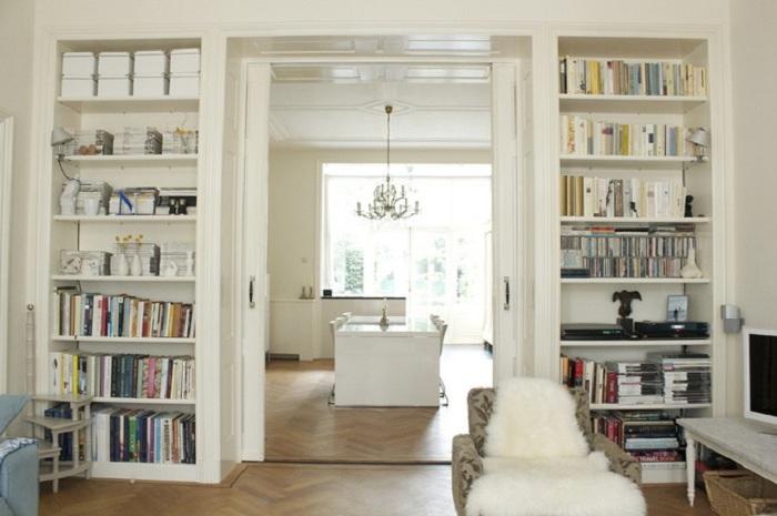 Прекрасная белоснежная комната с книжными стеллажами по обе стороны от дверной арки.