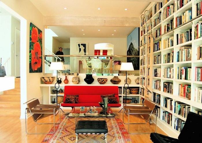 Сочетание белых и красных цветов в симпатичном оформлении комнаты с книжными полками и яркими маками на картине.