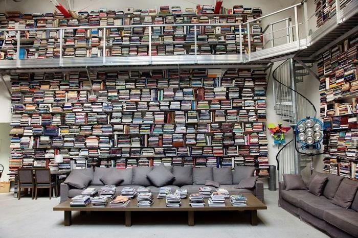 Двухэтажная комната с шикарным диваном по центру, заполнена книгами как на верхнем, так и на нижнем этажах.