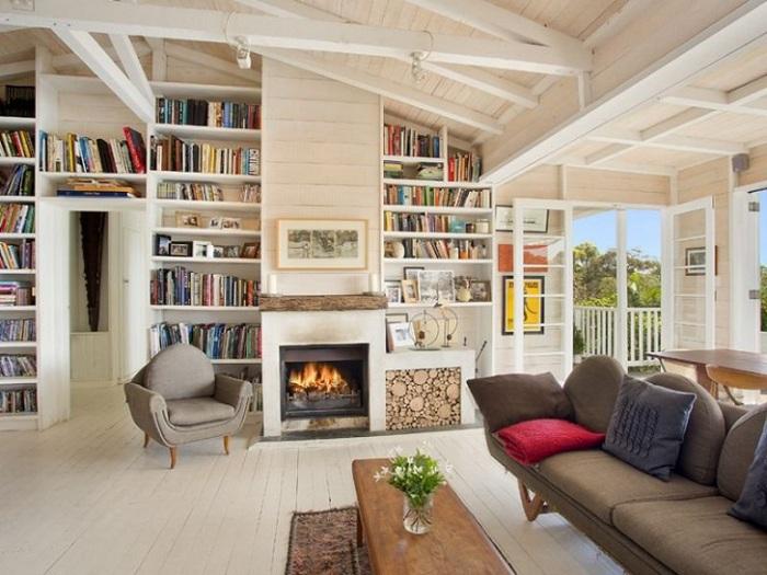 Симпатичная комната в молочно-сливочных тонах с камином и книжными полками, отличный вариант для интерьера.