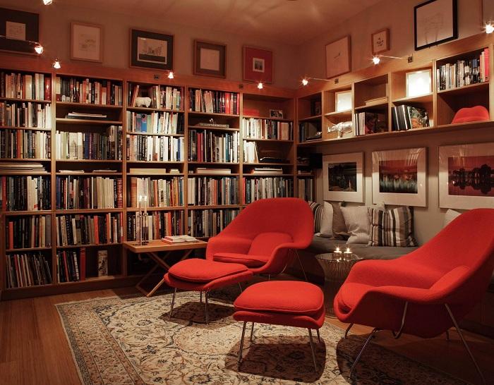 Прекрасная комната с книжными полками с симпатичными красными стульями для чтения обустроена специально для чтения книг.