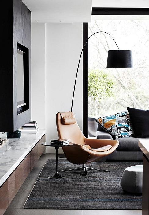 Современная и универсальная обстановка в комнате с крутым креслом для чтения.