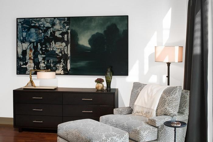 Интересный дизайн комнаты в черно-белых тонах с красивым серым креслом для чтения.