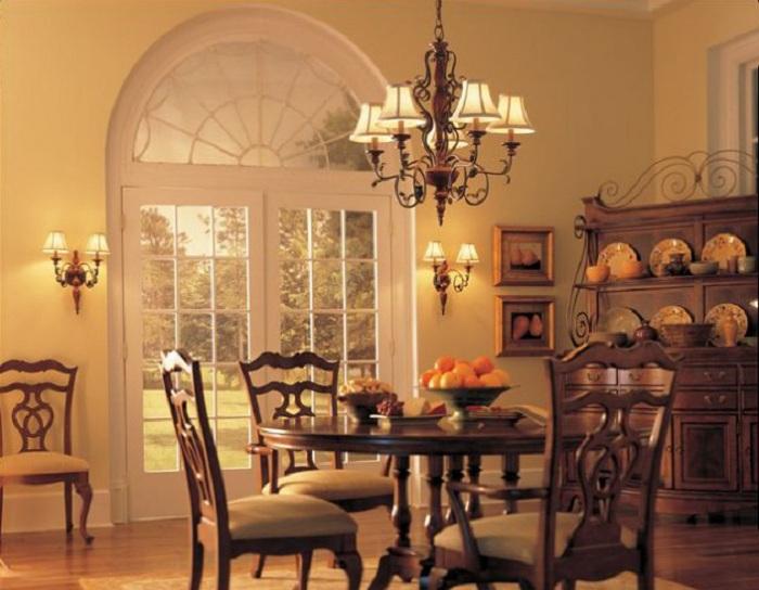 Уютная атмосфера в такой столовой комнате достигнута при помощи удачного сочетания цветов и материалов в интерьере и симпатичном дополнении люстры.