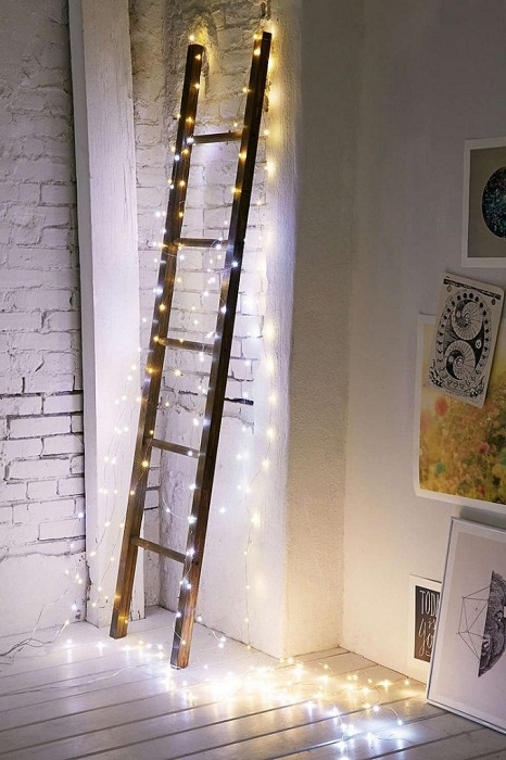 Отличный вариант создать новогоднюю атмосферу украсив лестницу гирляндой.