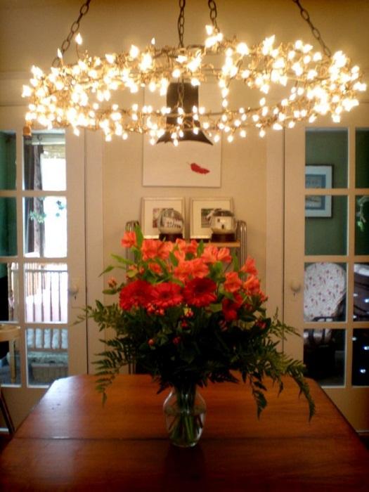 Простой, но притягательный интерьер столовой дополнен крутой люстрой.