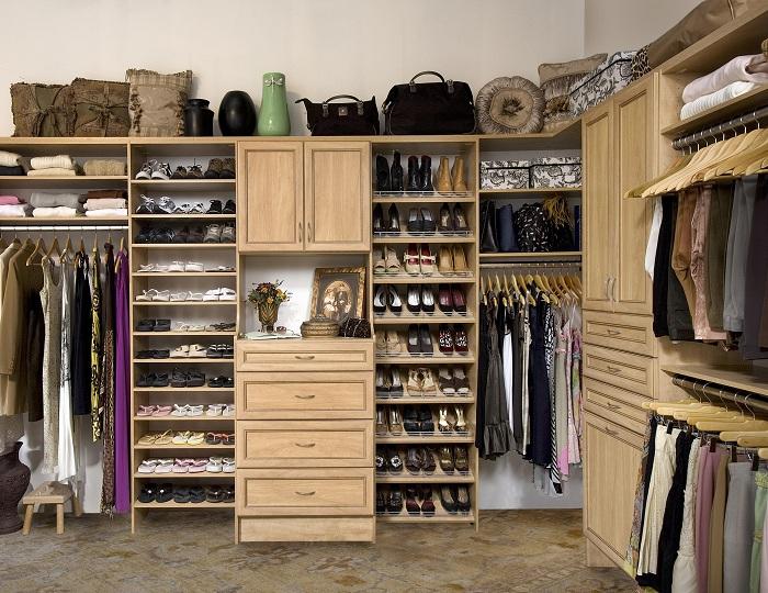 Симпатичное сочетание деревянных деталей интерьера с большим количеством одежды не мешает этой гардеробной не выглядеть загроможденной.