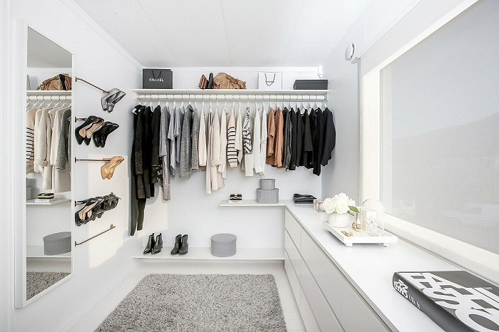 Уютная светлая комната для хранения вещей с полочками для обуви и удобными деталями интерьера.