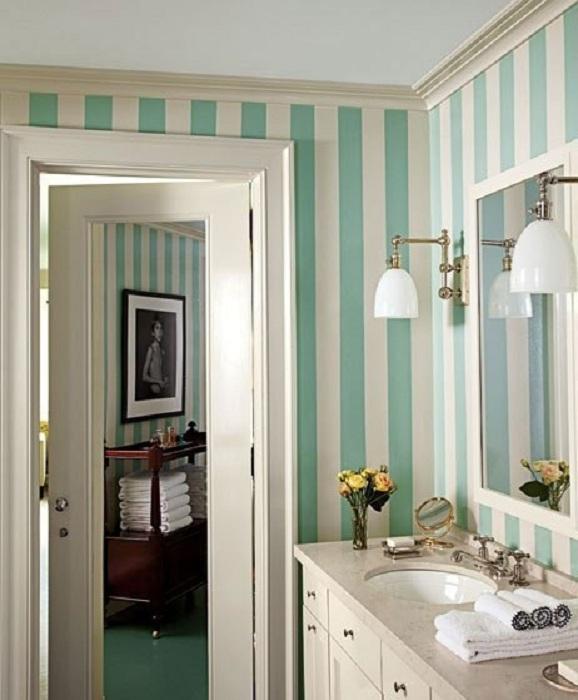 Необычное настроение в ванной комнате создано благодаря полосатым обоям в бело-бирюзовых тонах.