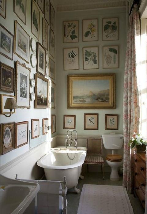Ванная комната обустроена благодаря оформлению стен при помощи множества рамок с различными изображениями.