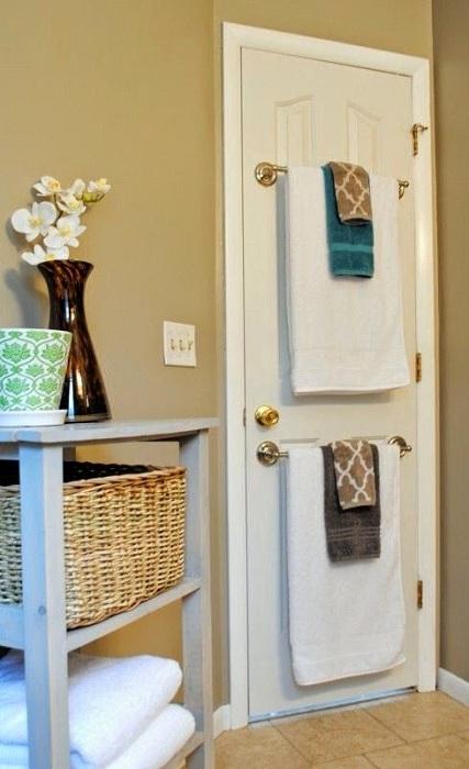 Экономить площадь ванной комнаты возможно при помощи различных способов, один из них, разместить полотенца на двери.