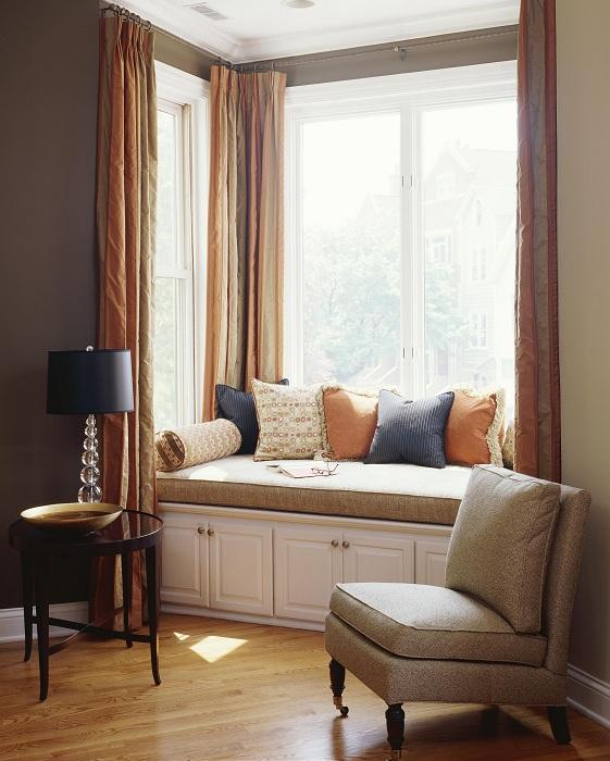 Прекрасная теплая и уютная обстановка в комнате с удобным местом для отдыха на подоконнике.