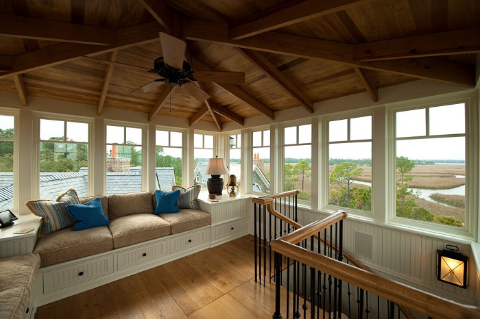 Отличный диванчик у окна под крышей дома, который станет любимым местом для отдыха.