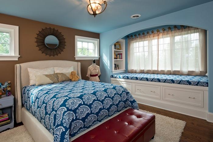 Интересное оформление комнаты в синих тонах с window seat, который украшает общую картину комнаты.