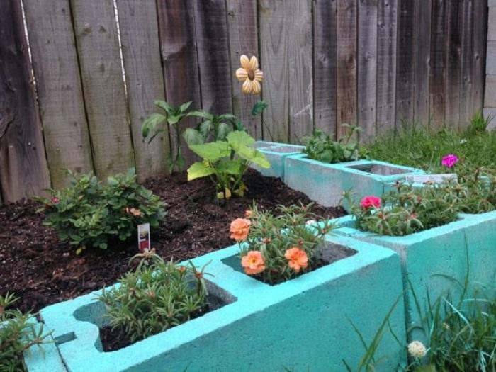 Прекрасный вариант рассадить цветы в обычные шлакоблоки, то что создаст интересный вариант декорирования двора.