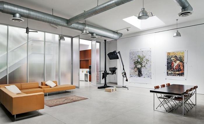 Гостиная комната облагорожена благодаря оформлению её в светло-серых тонах и интересному интерьеру, который украшен перегородкой.