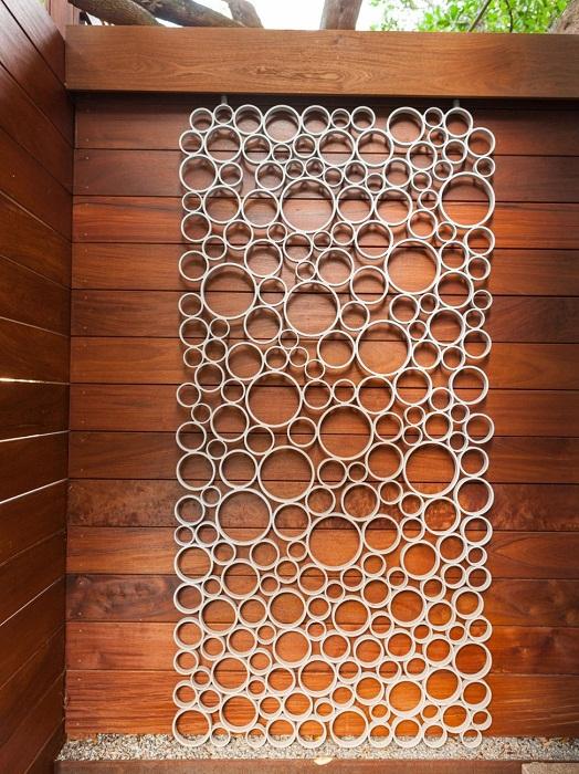 Украсить стену возможно благодаря ПВХ трубам, что создадут очаровательное настроение.